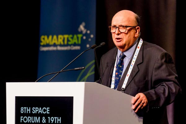 Man speaking at 8th space forum in front of SmartSat banner